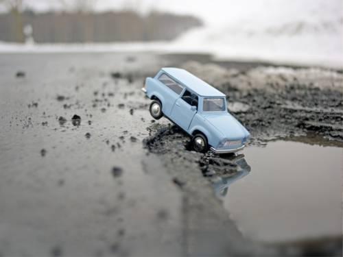 """Blauer Minitur-PKW der in eine Pfütze """"stürzt""""."""