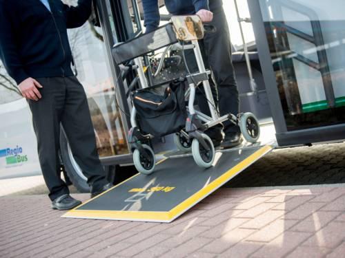 Ein Mann mir einem Rollator, der über eine Rampe aus einem Bus aussteigt. Direkt neben der Tür steht ein weiterer Mann. Von beiden Personen sind lediglich die Beine und ein Teil des Oberkörpers zu sehen.