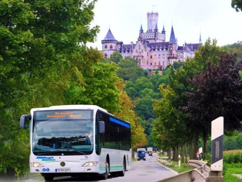 Ein Bus kommt auf einer Landstraße entgegen. Im Hintergrund befindet sich die Marienburg.