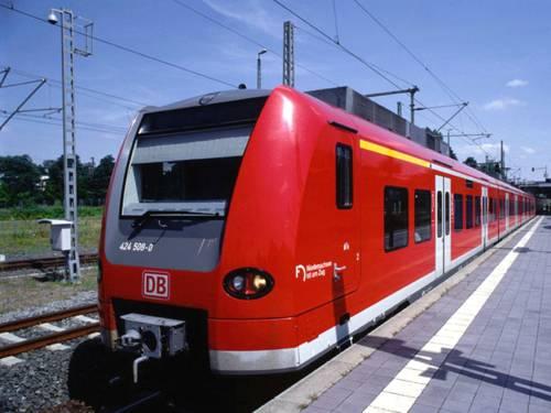 Das Schienenfahrzeug ist rot, im Hintergrund sind Bäume zu erkennen.