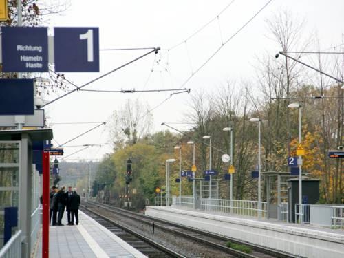 Blick auf den Bahnsteig des S-Bahnhofs Empelde. Links warten Menschen an Bahnsteig 1, rechts leuchtet ein rotes Signal an Bahnsteig 2, dazwischen verlaufen die Schienen.