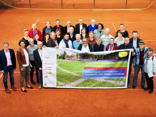 Eine Gruppe von Menschen steht auf einem Tennisplatz und hält ein Banner in den Händen
