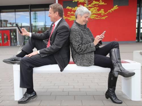 Ein Mann und eine Frau sitzen Rücken an Rücken auf einer modernen Bank vor einem Schulgebäude.