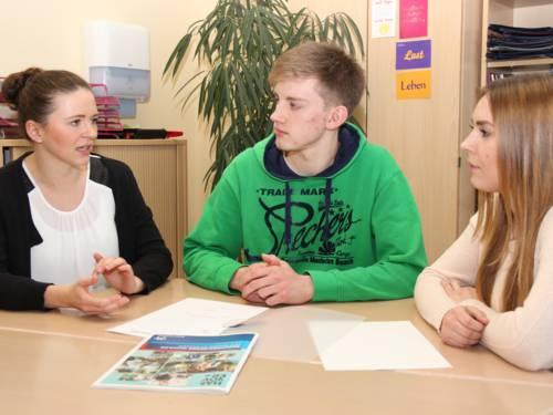 Zwei Frauen und ein junger Mann in einer Beratungssituation sitzen an einem Holztisch in einem Büro.