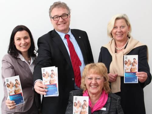 Drei Frauen und ein Mann. Alle vier lächeln und halten jeweils einen Flyer nach oben.