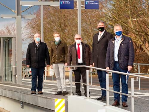 Fünf Herren mit Mund-Nasen-Schutz auf einem Hochbahnsteig in winterlicher Atmosphäre