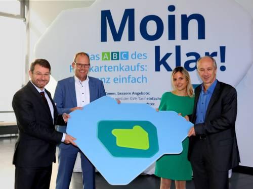Vier Personen halten ein Plakat in den Händen, das die neuen GVH-Tarifzonen darstellt