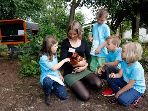 Eine junge Frau, die ein Huhn auf dem Arm hat und vier Kinder, die es sich interessiert ansehen bzw. es streicheln