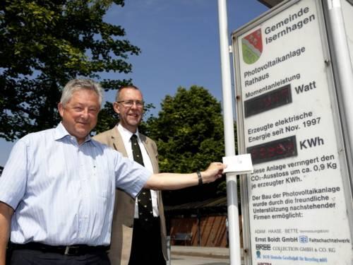 Arpad Bogya (links) und Prof. Dr. Axel Priebs stehen neben einer Infotafel mit digitaler Anzeige, die über die Photovoltaikanlage auf dem Rathausdach der Gemeinde Isernhagen informiert.