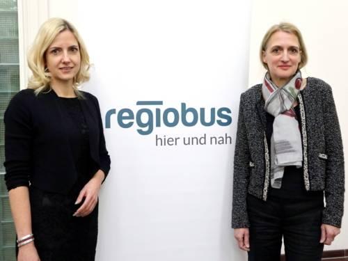 Zwei Frauen stehen vor einem Rollup-Banner der Regiobus.