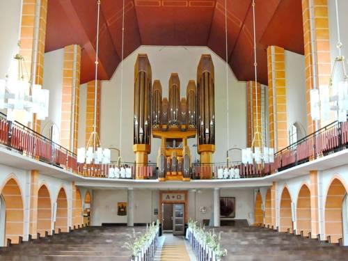 Blick über die Kirchenbänke zur Orgel.
