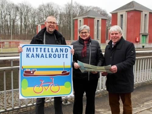"""Eine Frau und drei Männer. Der Mann Links hält ein Schild mit Aufschrift """"Mittellandkanalroute"""" in den Händen."""