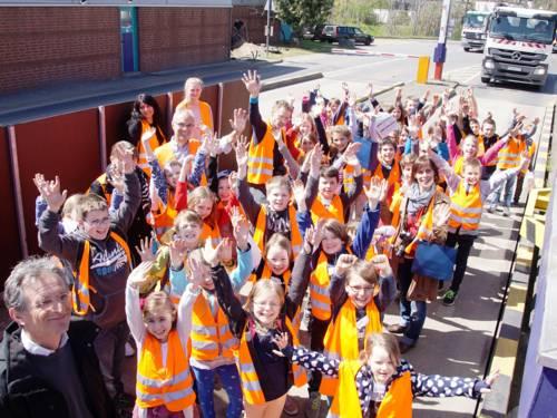 Eine Gruppe von fast vierzig Kindern und mehrere Erwachsene auf einer Anlieferwage einer Abfalldeponie. Alle tragen orange Sicherheitswesten und die meisten strecken ihre Arme in die Höhe.