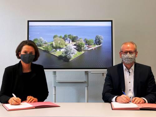Zwei Personen bei einer Vertragsunterzeichnung. Im Hintergrund zeigt ein Bildschirm eine Inselfestung - die Insel Wilhelmstein im Steinhuder Meer