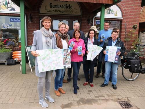 Eine kleine Gruppe Männer und Frauen, die eine Broschüre in den Händen halten, vor einem Laden in einem Backsteingebäude.