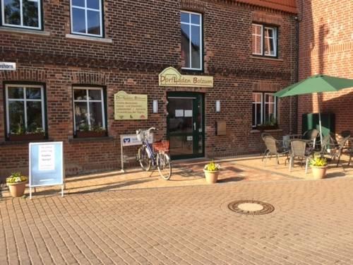 Ein rotes Backsteingebäude, davor ein Werbeaufsteller, ein Fahrrad und eine Sitzmöglichkeit aus Gartenstühlen, Tischen und einem Sonnenschirm