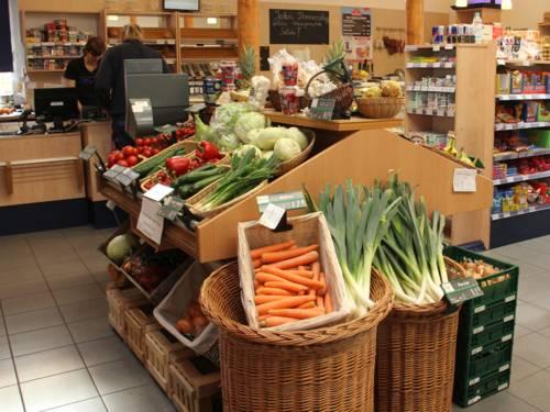 Lauch und Möhren in Holzkisten in einem Laden, im Hintergrund weitere Produkte