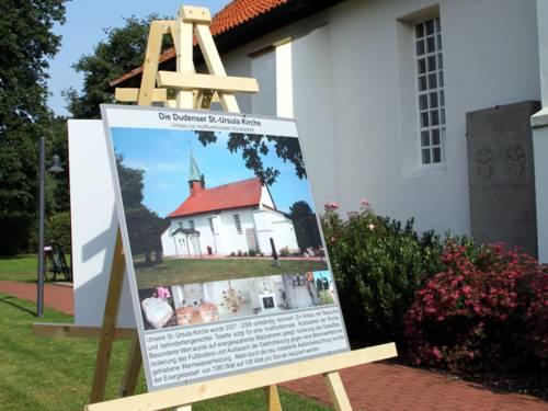 Infotafel auf einer Staffelei vor der weißen Fassade eines Kirchengebäudes.