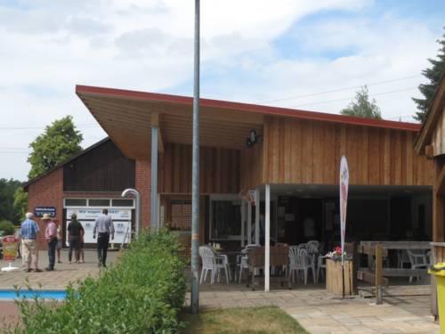 Holzgebäude neben einem Schwimbecken.