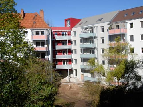 Mehrgeschossige weisse Wohnhäuser mti farbigen Balkons, im Vordergrund Bäume