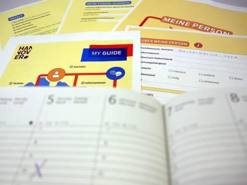 Blick über einen geöffneten Kalender (unscharf): Einzelne Seiten der Beratungsmappe MY GUIDE liegen ausgebreitet und sind teilweise ausgefüllt (scharfer Bildbereich).