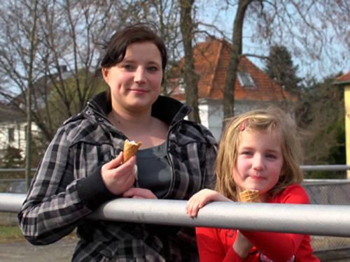 Eine Mutter und ihre Tochter, beider mit einer Eiswaffel in der Hand, stehen draußen an einem Geländer. Im Hintergrund sind einige Bäume ohne Grün zu sehen und ein weißes Wohnhaus mit spitzem roten Dach.