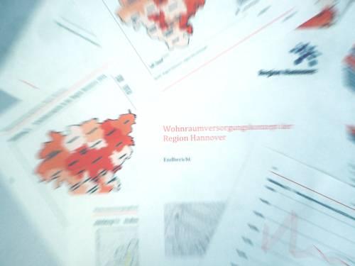 """Deckblatt und einzelne Seiten des Wohnraumversorgungskonzeptes der Region Hannover liegen auf einem Tisch aus. Von einem zentralen Punkt aus wird die Szene dynamisch auseinandergerissen, sodass nur die Begriffe """"Wohn"""" und """"Region"""" scharf zu erkennen sind, nach außen hin nimmt die Unschärfe zu."""