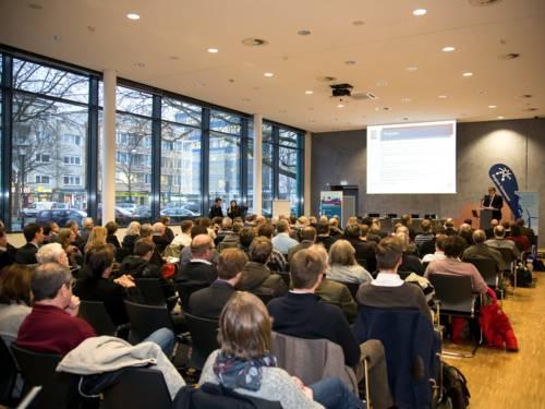 Regionspräsident Hauke Jagau eröffnet von einem Podium die Informationsveranstaltung Energiegenossenschaften, davor sitzt ein breites Publikum .