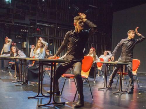 """Mädchen und Jungen erheben sich von ihren Stühlen und beginnen zu tanzen. Das """"Klassenzimmer"""" steht auf einer Theaterbühne."""