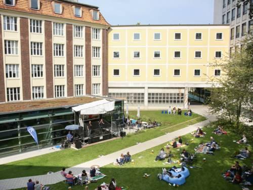 Eine Bühne zwischen Gebäuden in einem Innenhof. Menschen sitzen davor auf dem Rasen.