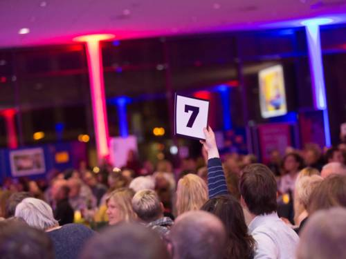 Ein bunt beleuchteter Raum mit vielen Menschen. Eine Person hält einen Zettel mit der Zahl Sieben in die Höhe.