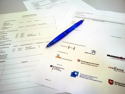 Einzelne Blätter eines Fragebogens liegen auf einem Tisch, darauf liegt ein Kugelschreiber.