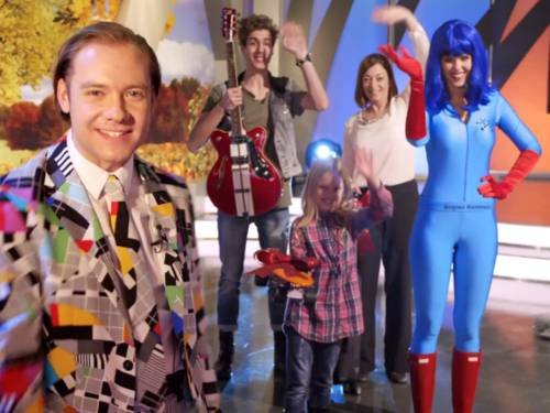 Ein Quizmaster, zwei Kandidaten, eine Superheldin und ein Kind stehen in einem Fernsehstudio und blicken in die Kamera. Bid auf den Quizmaster (links) winken alle.