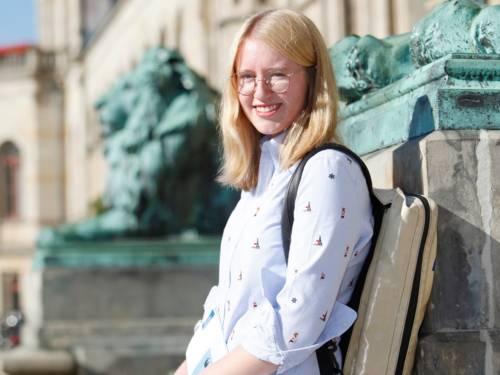 Porträtfoto eines Mädchens vor einem Gebäude mit steinernen Löwen.