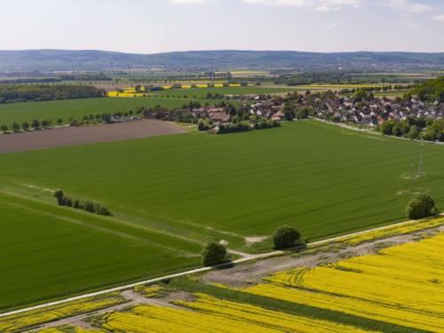 Luftbild der Ortschaft Göxe, im Hintergrund Windkraftanlagen und der Deister