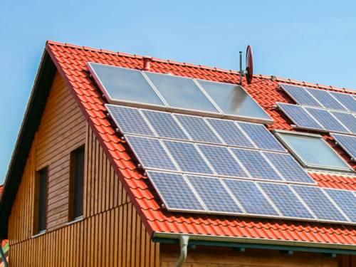 Rotes Ziegeldach eines Hauses auf dem diverse Solaranlagen montiert sind
