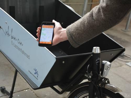 Korb eines Lastenfahrrads und eine Hand, die ein Mobiltelefon hält, auf dem eine Karte zu sehen ist