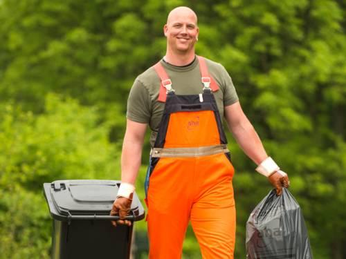 Ein Mitarbeiter der Abfallwirtschaft Region Hannover (aha) bewegt einen Restabfallsack und eine Restabfalltonne.