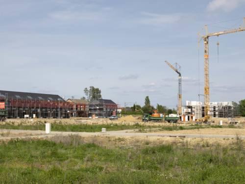 Gebäude im Rohbau, Kran und LKW