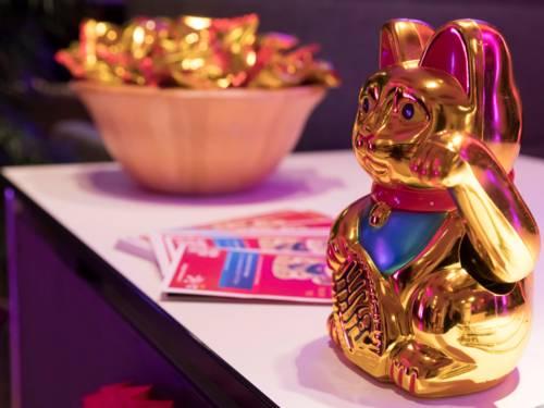 Figur einer goldenen Katze mit rotem Halsband steht auf einem Tisch, außerdem sind Flyer und eine Schale mit Glückskeksen auf dem Tisch.