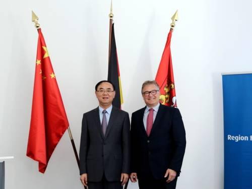Zwei Männer stehen nebeneinander vor Fahnen.