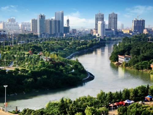 Chinesische Stadt mit einem Fluss im Vordergrund.