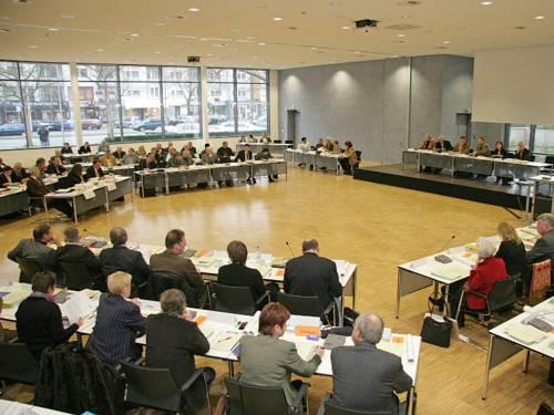 Mitglieder der Regionsversammlung sitzen auf Stühlen und an Tischen, die kreisförmig aufgestellt sind.