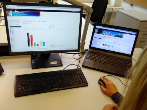 Eine Frau schaut sich Wahlergebnisse an einem Laptop und einem Bildschirm an.