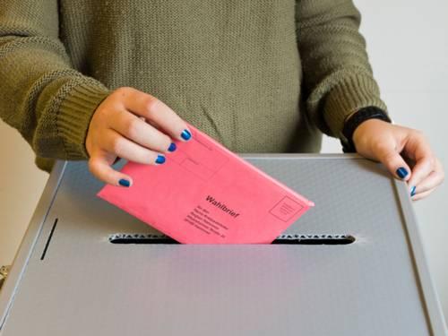 Eine Person wirft ihren verschlossenen Stimmzettel in die Wahlurne.