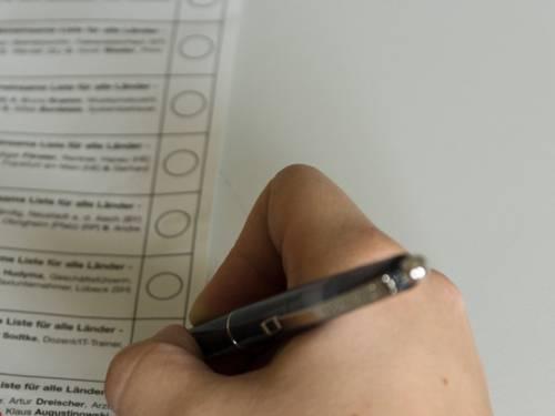 Die Hand einer Person, die gerade mit einem Kugelschreiber ihr Kreuz auf einem Stimmzettel setzen möchte.