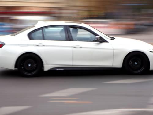 Ein weißes Auto fährt auf einer Straße. Durch die Bewegung ist der Hintergrund unscharf.