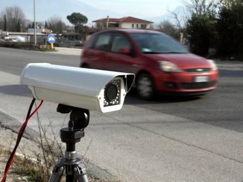 Ein mobiles Gerät zur Geschwindigkeitskontrolle ist neben einem Fahrtstreifen aufgebaut, dahinter fährt ein rotes Auto.