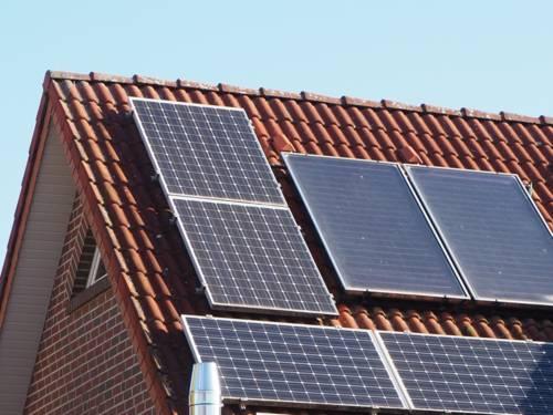 Photovoltaikmodule für Strom (links und unten) und Solarthermie für Wärme sind auf einem Hausdach montiert.