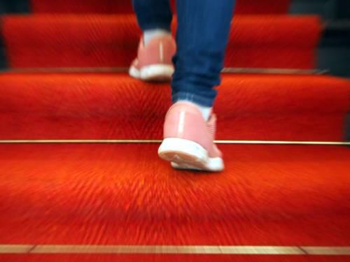 Zwei Füße stecken in Turnschuhen und bewegen sich schnell eine Treppe hinauf. Die Treppe ist mit rotem Teppich ausgelegt.